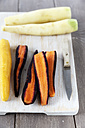 Different sorts of whole and sliced carrots, kitchen knife on chopping board and wooden table - EVGF000543