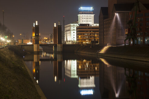 Germany, North Rhine-Westphalia, Duisburg, Inner harbour, View to Schwanentorbruecke, Kontorhaus by night - WIF000612