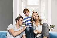 Portrait of young family sitting on their couch at living room - MFF001075