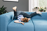 Boy rollicking around on blue couch in living room - MFF001072
