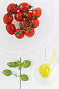 Fresh bunch tomatoes in a colander and oil - EVGF000521