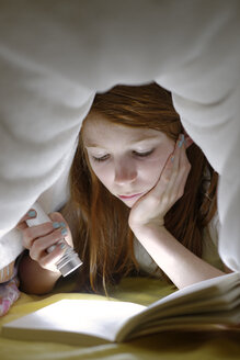 Portrait of girl reading a book secretly in bed under the blanket - LBF000693