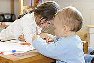 Brother and sister drawing at table - LAF000798