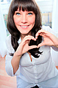 Portrait of smiling dark-haired woman forming heart with her hands - AFF000069