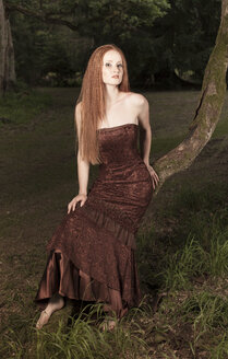 Young woman with evening dress sitting on tree trunk in park by night - FCF000055