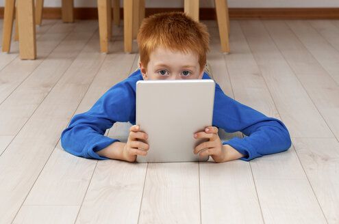 Little boy with tablet computer lying on wooden floor - JED000195