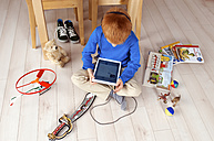 Little boy sitting on wooden floor using tablet computer - JED000188
