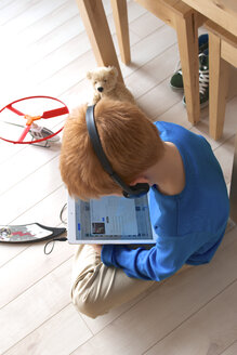 Little boy with headphones sitting on wooden floor using tablet computer, elevated view - JED000189