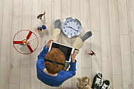 Little boy with headphones sitting on wooden floor using tablet computer, elevated view - JED000194