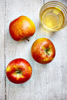 Three apples and a glass of apple juice on grey wood, elevated view - KSWF001249
