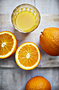 Oranges, halves of oranges and a glass of orange juice on grey wood, elevated view - KSWF001253
