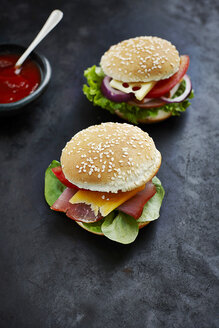 Two prepared burgers, mustard and ketchup on dark ground - KSWF001261
