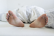 Feet of young woman sticking out of bed - FLF000412