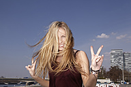 Happy young woman making peace sign - FMKF001166