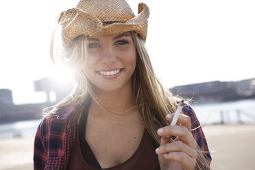 Portrait of smiling young woman wearing cowboy hat - FMKF001174