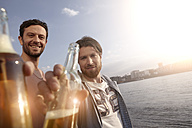 Portrait of two friends with beer bottles on riverbank - FMKF001183