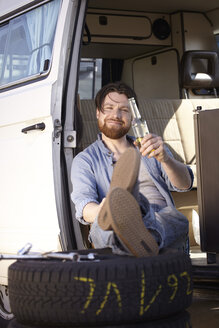 Man sitting in car with tyre and beer bottle - FMKF001187