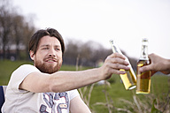 Two friends with beer bottles outdoors - FMKF001194