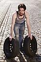 Man rolling car tyres - FMKF001199