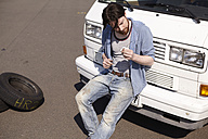 Man leaning against car looking at dipstick - FMKF001205