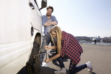 Smiling couple changing car tyre at minivan - FMKF001218