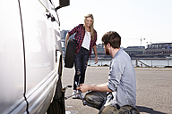 Smiling couple changing car tyre at minivan - FMKF001221