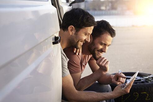 Two men sitting in car looking at digital tablet - FMKF001224