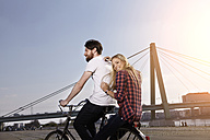 Happy couple riding bicycle on riverbank - FMKF001228