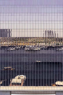 UAE, Dubai, Bur Dubai, Reflections in glass front of highrise building - THAF000290