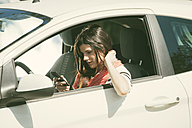 Spain, Barcelona, Young woman with cell phone in car - EBSF000226