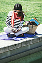 Spain, Barcelona, Young woman sitting on wall reading book - EBSF000233