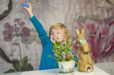 Happy blond boy with Easter bunny holding egg - MJF000963