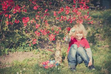 Boy in garden holding Easter egg - MJF000977
