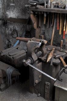 Germany, Bavaria, Josefsthal, bench vice, hammer and anvil beaks at historic blacksmith's shop - TCF003947