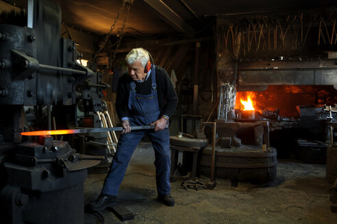 Germany, Bavaria, Josefsthal, senior  blacksmith at work in historic blacksmith's shop - TCF003960