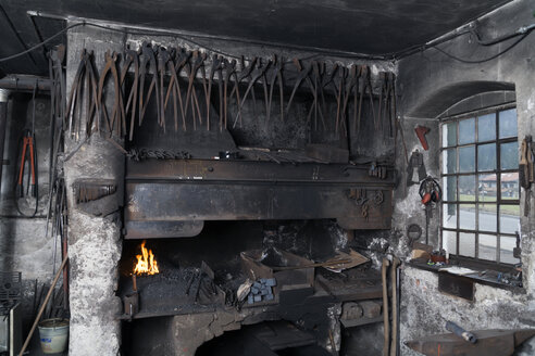 Germany, Bavaria, Josefsthal, row of grippers hanging over forge at historic blacksmith's shop - TCF003964