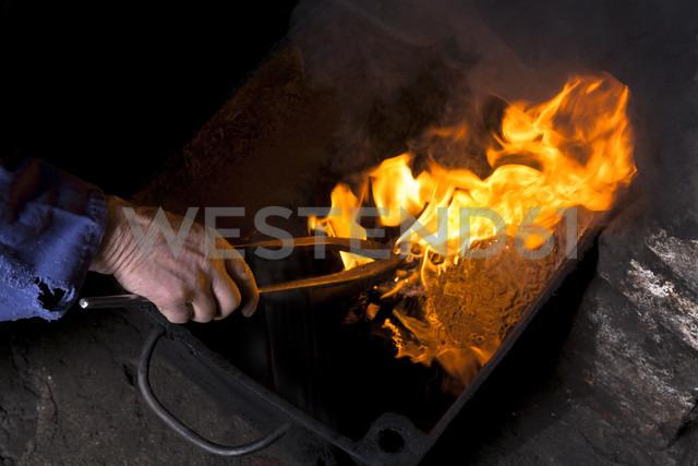Germany, Bavaria, Josefsthal, burning hardening oil at historic blacksmith's shop - TCF003970 - Tom Chance/Westend61