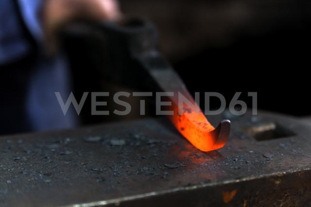 Germany, Bavaria, Josefsthal, glowing pickaroon at historic blacksmith's shop - TCF003986