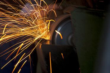 Germany, Bavaria, Josefsthal, sparkles at grinder in historic blacksmith's shop - TCF003929