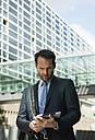 Businessman using digital tablet outdoors - UUF000356
