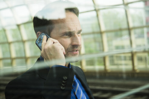 Businessman at train station on the phone - UUF000372