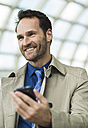 Smiling businessman holding cell phone - UUF000381