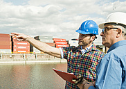 Two men with safety helmets talking at container port - UUF000408