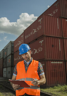 Man with clipboard wearing reflective vest at container port - UUF000410