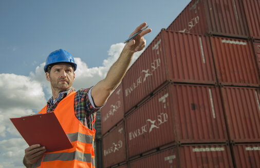 Man with clipboard wearing reflective vest at container port - UUF000413