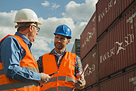 Two men with safety helmets and reflective vests talking at container port - UUF000415