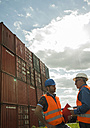 Two men with safety helmets and reflective vests talking at container port - UUF000417