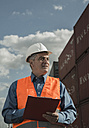 Man with clipboard wearing reflective vest at container port - UUF000420