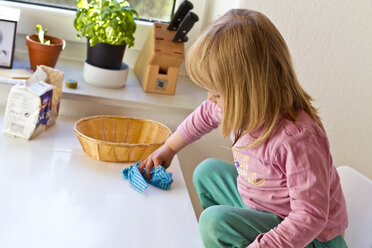 Little girl wiping kitchen table - JFE000339