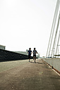 Young man and teenager running on bridge - UUF000400
